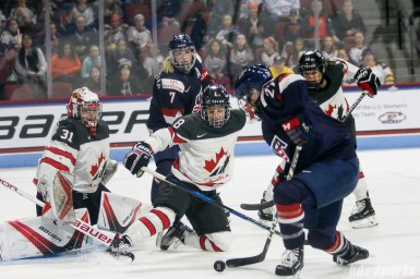 Team Canada goalie Genevieve Lacasse (31) and defender Laura Fortino (8) defend the goal against Team USA forward Annie Pankowski (27)