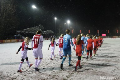 The starting XI for the Ajax and FC Twente teams walk out onto the field