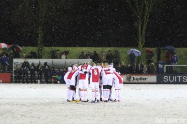 The Ajax starting XI huddle before the start of the game