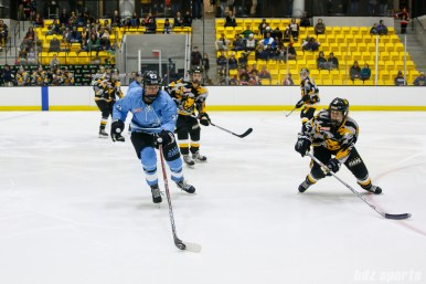 Buffalo Beauts forward Corinne Buie (23) controls the puck while being defended by Boston Pride defender Alyssa Gagliardi (2)