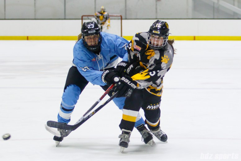 Boston Pride forward Emily Field (15) takes a shot on goal while being challenged by Buffalo Beauts forward Corinne Buie (23)