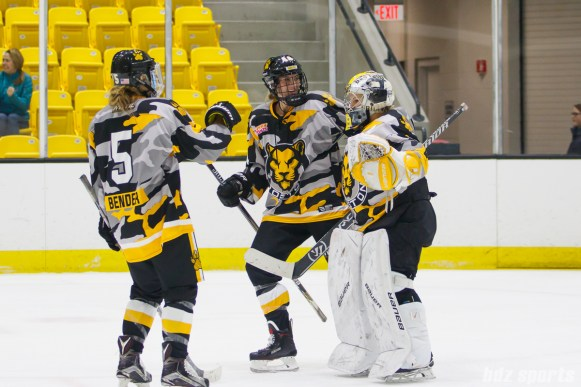 Boston Pride defenders Alexandra Bender (5) and Paige Harrington (44) congratulate goalie Brittany Ott (29) after they defeated the Buffalo Beauts 3-2 on December 2, 2017