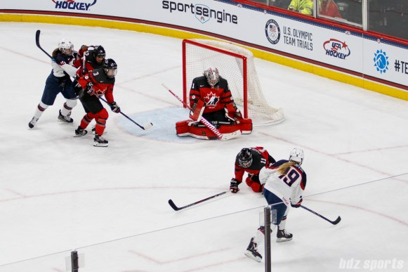 Team Canada goalie Shannon Szabados (1) stops a shot from Team USA defender Gigi Marvin (19)