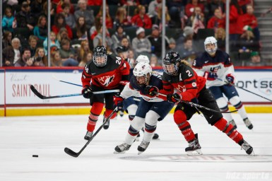 Team USA forward Dani Cameranesi (24) shields Team Canada forward Meghan Agosta (2) off the puck