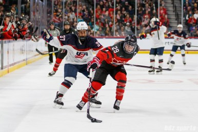 Team Canada forward Marie-Philip Poulin (29) keeps the puck away from Team USA forward Amanda Pelkey (37)