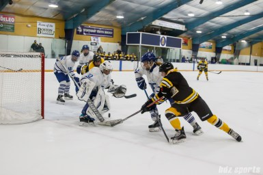 The puck bounces between Toronto Furies goalie Sonja van der Bliek (30), Furies defender Sydney Kidd (8), and Boston Blades forward Elizabeth Aveson (4)