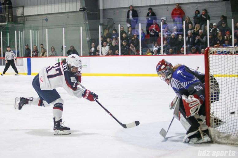 Team USA forward Amanda Pelkey (37) slips the puck past Team NWHL goalie Katie Fitzgerald (35)