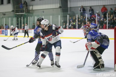 Team USA forward Kelly Pannek (12) and Team NWHL players Jenny Ryan (4) and Katie Fitzgerald (35) keep an eye on the puck