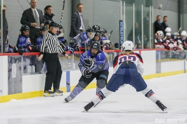 Team NWHL forward Hayley Scamurra (24) flicks the puck past Team USA defender Kacey Bellamy (22)