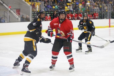 Boston Pride defender Paige Harrington (44) and Metropolitan Riveters forward Harrison Browne (24) keep an eye on the puck