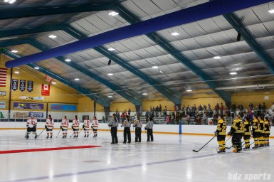 The starting lineups for the Boston Blades and Kunlun Red Stars stand for the playing of the national anthems