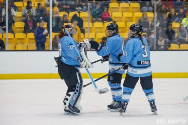 Buffalo Beauts defenders Jordyn Burns (17) and Sarah Edney (3) congratulate goalie Amanda Leveille (28) after the Beauts defeated the Boston Pride 6-2