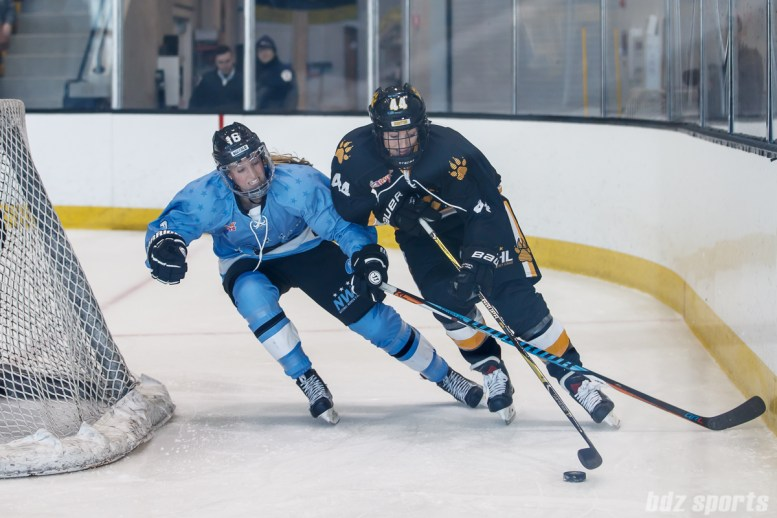 Boston Pride defender Paige Harrington (44) looks to bring the puck around the back of the net while Buffalo Beauts forward Maddie Elia (16) defends