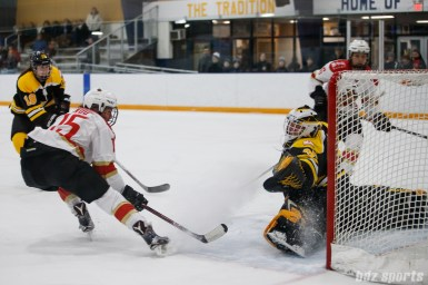 Boston Blades goalie Lauren Dahm (35) stretches out cover the goal from oncoming Kunlun Red Star forward Madison Woo (15)