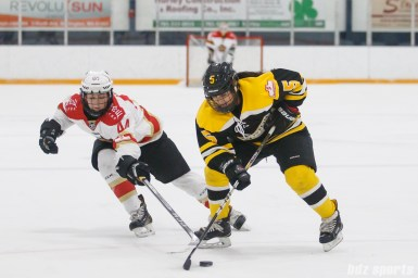 Boston Blades forward Michelle Ng (5) controls the puck for the Blades while being defended by Kunlun Red Star forward Zoe Hickel (44)
