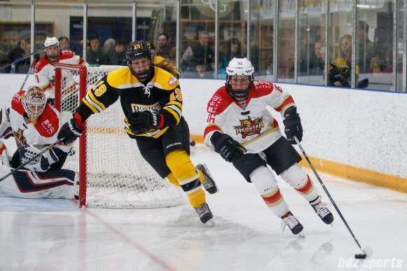 Kunlun Red Star forward Kelli Stack (16) brings the puck around the Red Star net