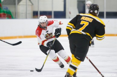 Kunlun Red Star defender Taylor Marchin (11) cuts across with the puck