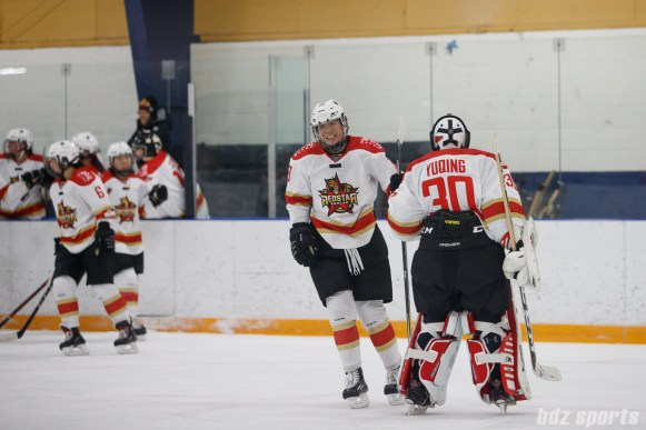 Kunlun Red Star defender Zhixin Liu (93) fist bumps teammate goalie Yuqing Wang (30) after scoring a goal