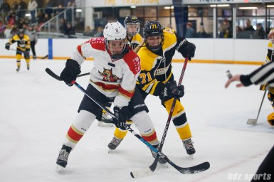 Kunlun Red Star forward Alex Carpenter (9) looks for the puck while being defended by Boston Blades defender Kelly Kittredge (71)