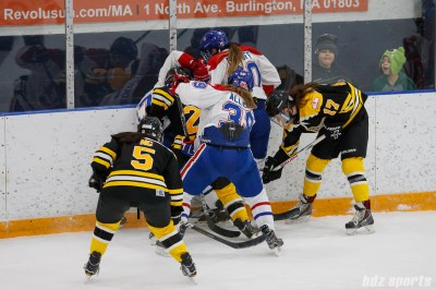 Montreal Les Canadiennes and Boston Blades players battle for the puck against the boards