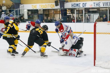 Boston Blades forward Kate Leary (28) pushes the puck past Montreal Les Canadiennes goalie Emerance Maschmeyer (38) for Boston's third goal of the game