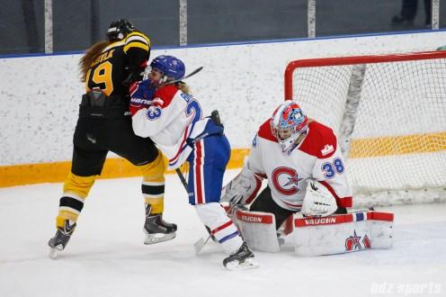 Montreal Les Canadiennes goalie Emerance Maschmeyer (38) blocks the puck while Les Canadiennes defender Sophie Brault (23) shields off Boston Blades forward Taylor Wasylk (19)