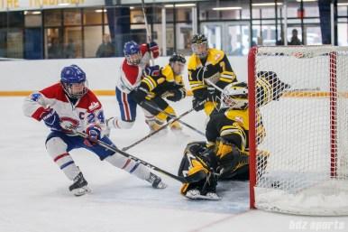 Montreal Les Canadiennes forward Ann-Sophie Bettez (24) slips the puck past Boston Blades goalie Lauren Dahm (35)