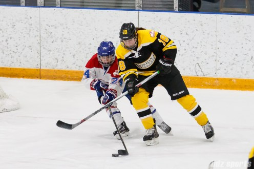 Boston Blades defender Taryn Harris (18) challenges Montreal Les Canadiennes forward Ann-Sophie Bettez (24) for the puck