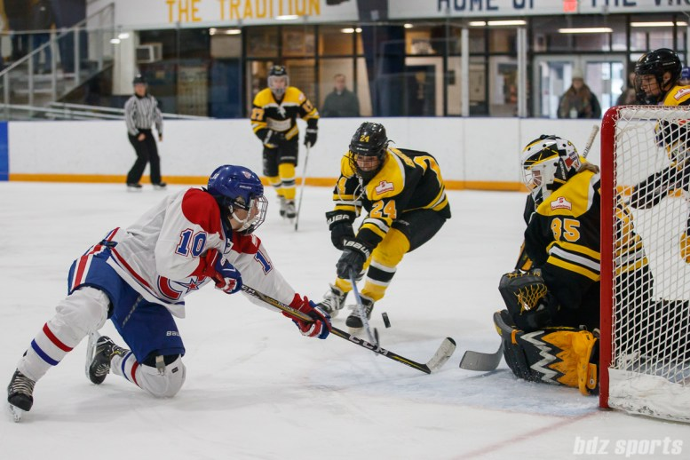 Montreal Les Canadiennes forward Noemie Marin (10) and Boston Blades defender Kristina Brown (24) battle for a loose puck in front of the goal