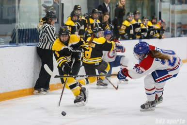 Boston Blades forward Courtney Turner (3) looks to send in the puck while being defended Montreal Les Canadiennes forward Jordanna Peroff (20)