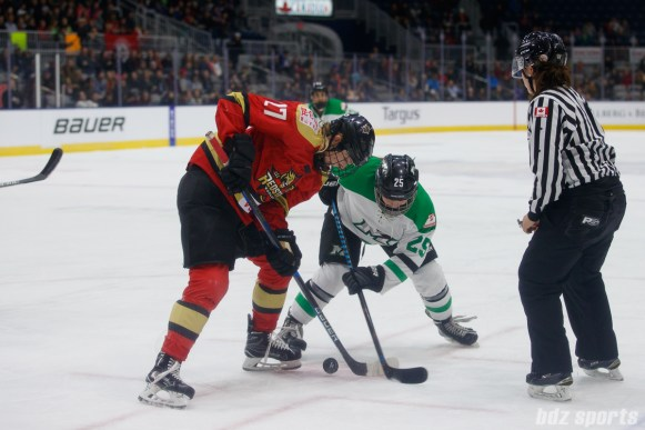 Kunlun Red Star forward Shiann Darkangelo (27) and Markham Thunder forward Taylor Woods (25) take a face-off