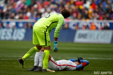 Team France goalie Sarah Bouhaddi (16) checks on Team USA forward Alex Morgan (13) after she is injured during a play