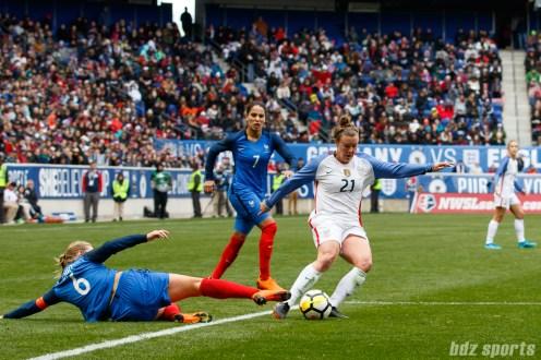 Team USA forward Savannah McCaskill (21) avoids a tackle from Team France midfielder Amandine Henry (6)