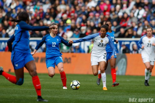 Team USA forward Christen Press (23) challenges Team France midfielder Gaetane Thiney (12) for the ball