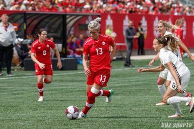 Team Canada midfielder Sophie Schmidt (13) and Team Germany midfielder Kristin Demann (6)
