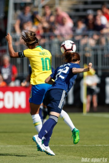 Team Japan defender Risa Shimizu (22) and Team Brazil forward Marta (10)