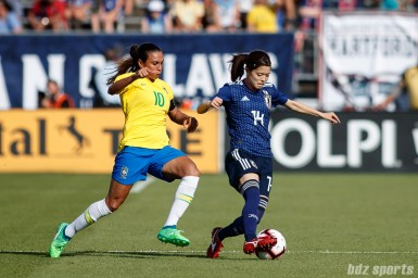 Team Japan midfielder Yui Hasegawa (14) and Team Brazil forward Marta (10)