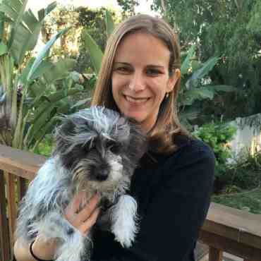 Dr Nicole Schiff holding a dog and smiling at the camera