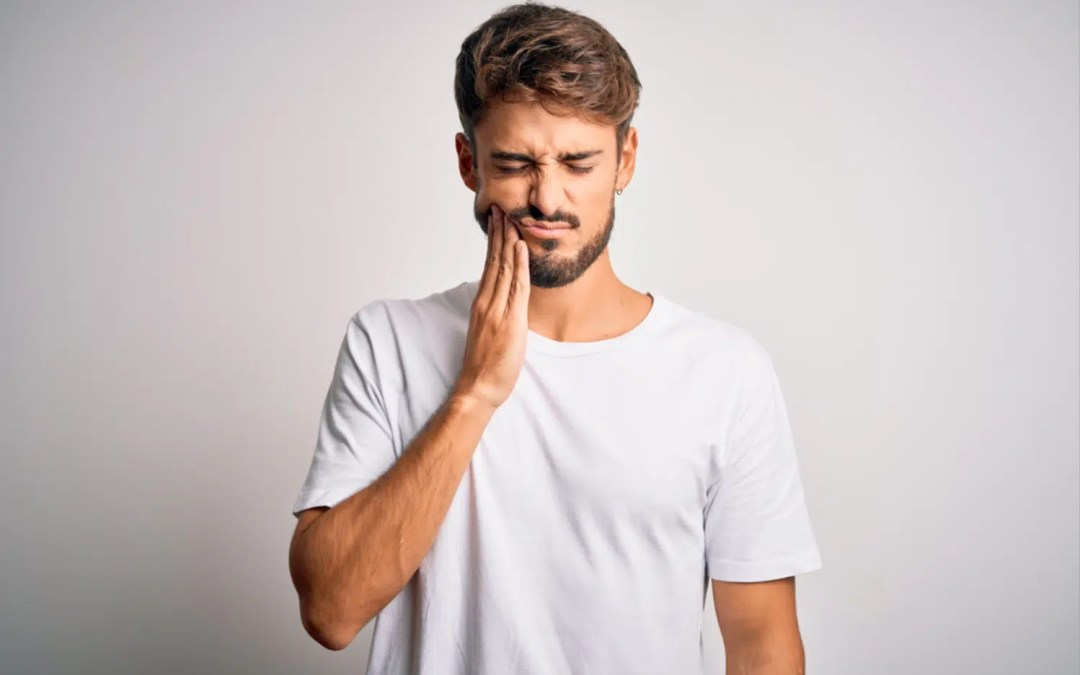 a man holding the side of his cheeks because of tooth pain