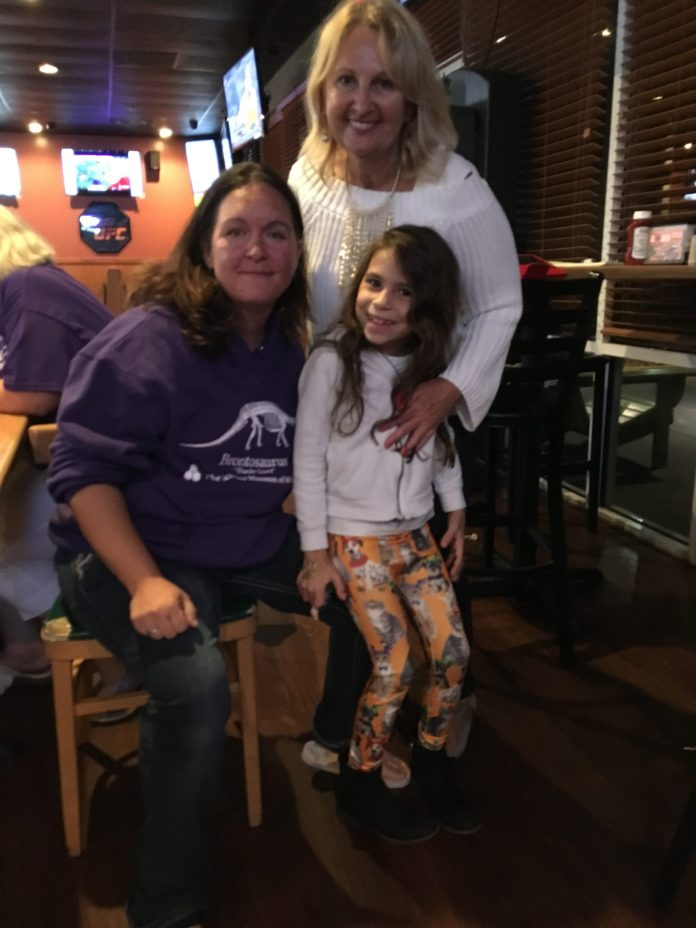 BEACON PHOTO/AL EVERSONAwaiting final results — With only one Deltona precinct remaining to be counted, Heidi Herzberg, standing, celebrates her apparent victory in the Deltona mayoral race with her niece Kaete Herzberg and Brooke Light.