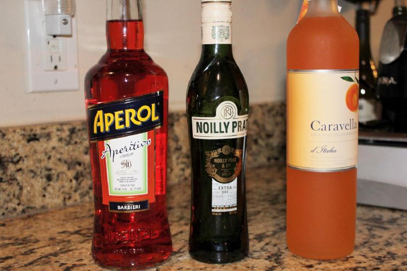 Bottles of Aperol, vermouth, and orangecello on a counter