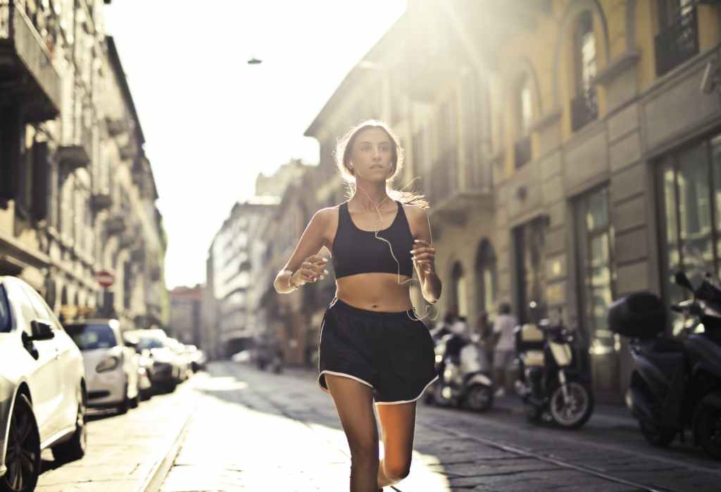 photo of woman listening to music on earphones jogging down a paved street
