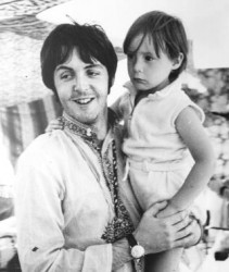 Paul McCartney carrying a young Julian Lennon