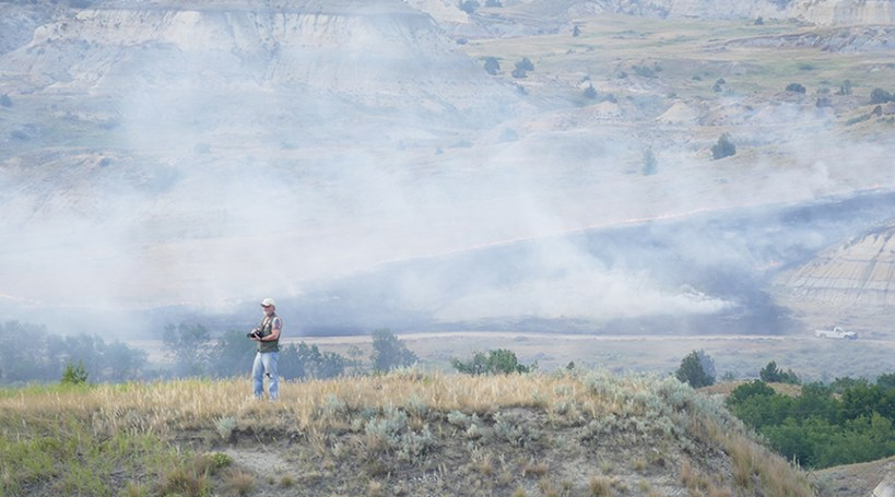 Standing over the magpie fire on a hilltop.