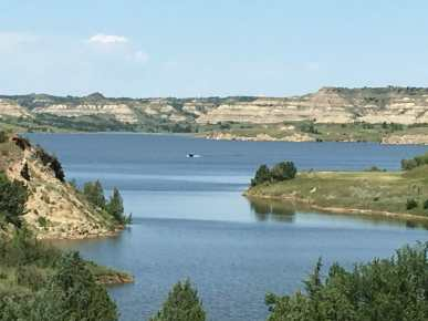 The rugged badlands meet the blue waters of Lake Sakakawea at Little Missouri Bay.