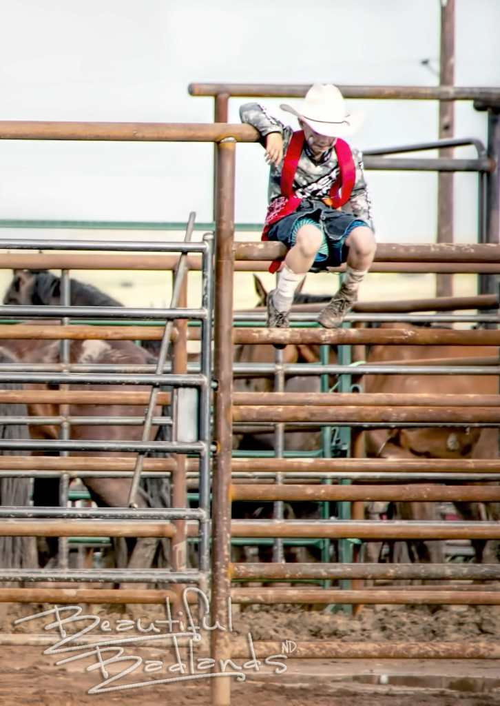 lil rodeo clown sits on fence at Killdeer Mountain Roundup Rodeo