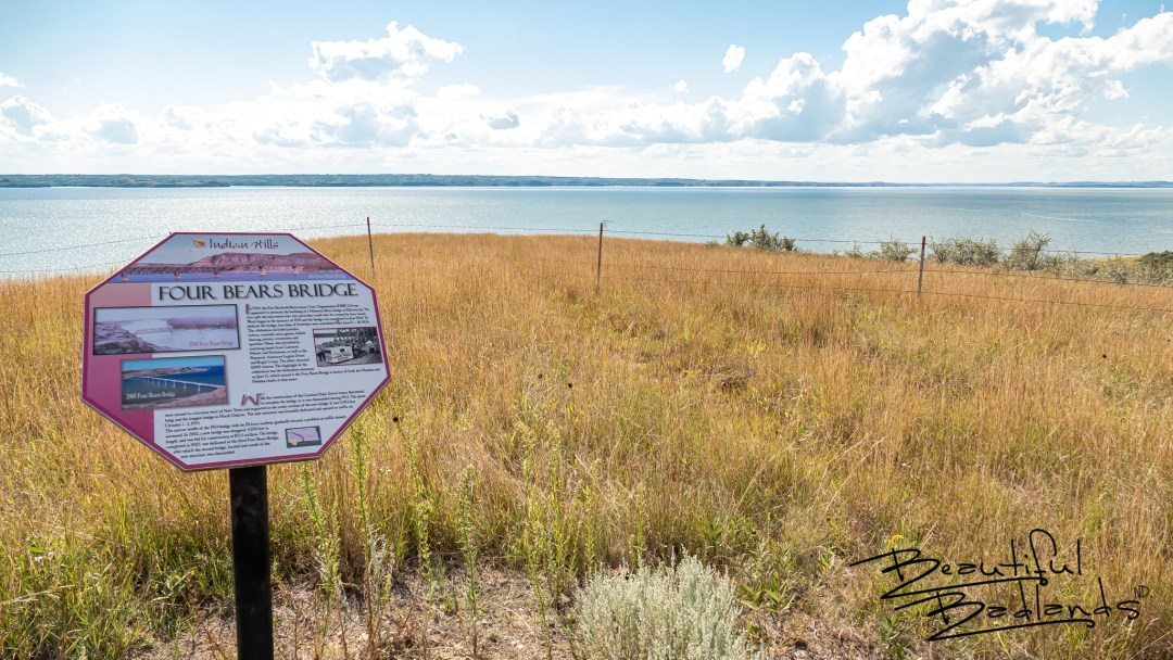 An informational sign on the Nux Baa Ga Trail relates the history of Four Bears Bridge which spanned the Missouri River at this area. The bridge was relocated to New Town before Lake Sakakawea flooded the area, submersing US Highway 8 and the town of Elbowoods at this location.