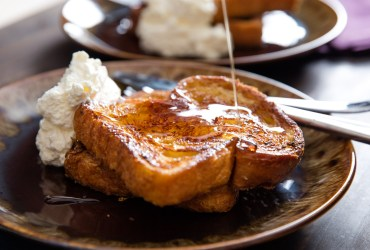 Thick, tender, custardy slices of challah or brioche, perfectly browned and flavored with orange zest, rum, and a trio of spices. This is special-occasion French toast.