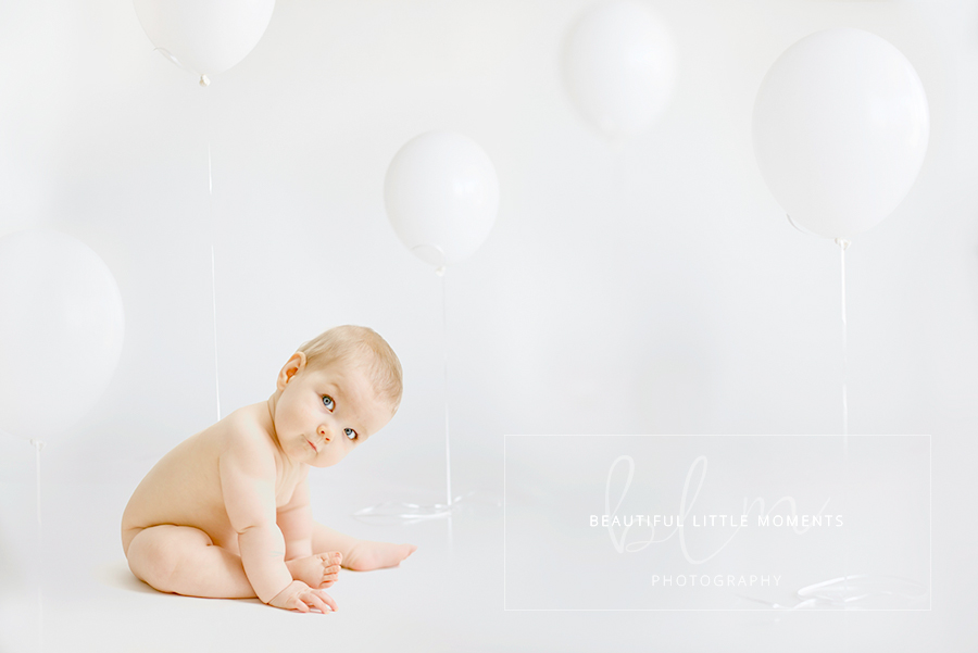 white balloons and baby first birthday photo shoot