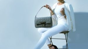 woman sitting on stool holding a handbag